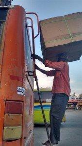 Bagageiro do ônibus. Observem a forma como o pobre homem leva a caixa para cima