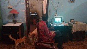 Em uma casa muito escura, com a Bíblia sobre a mesa, em meio ao cachorro e alguns gatos, o Joseph assiste programa evangélico americano