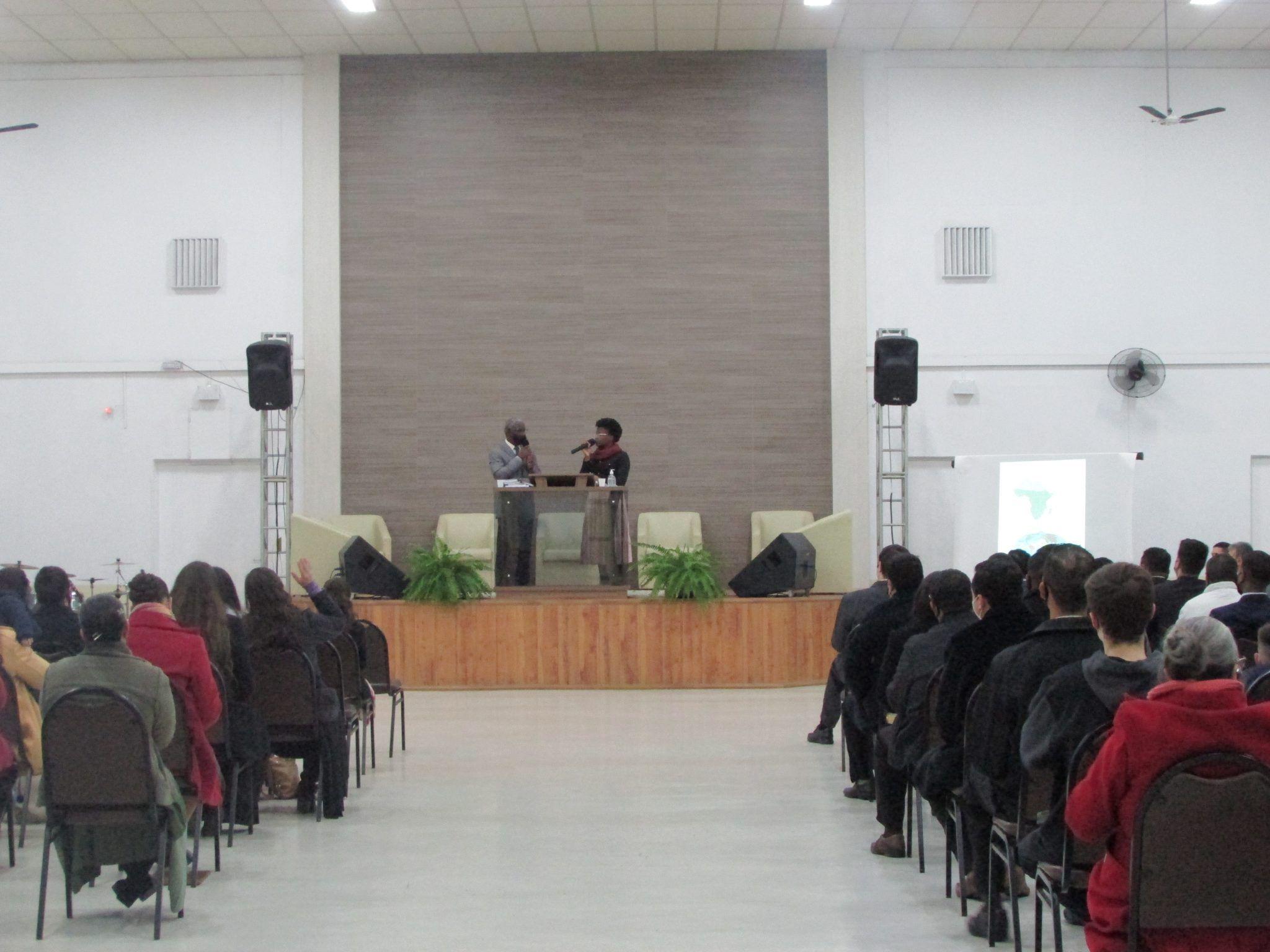 Pr. Hubert Gbenakou ministrando a Palavra de Deus em francês e irmã Grace Gbenakou traduzindo para o português.